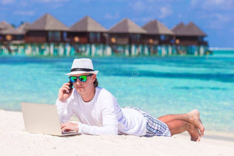 研究膝上型计算机的年轻人在热带海滩近 免版税库存图片