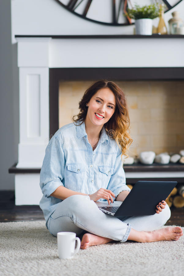 研究膝上型计算机的年轻美丽的偶然妇女坐地板在房子里 库存图片