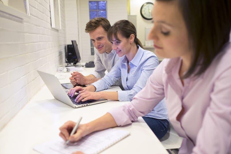 研究膝上型计算机的Businessteam在办公室 库存照片