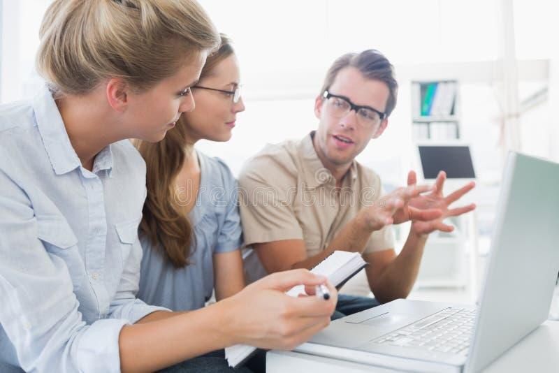 研究计算机的三青年人 库存图片