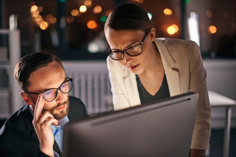 研究计算机的两个同事在晚上 库存照片