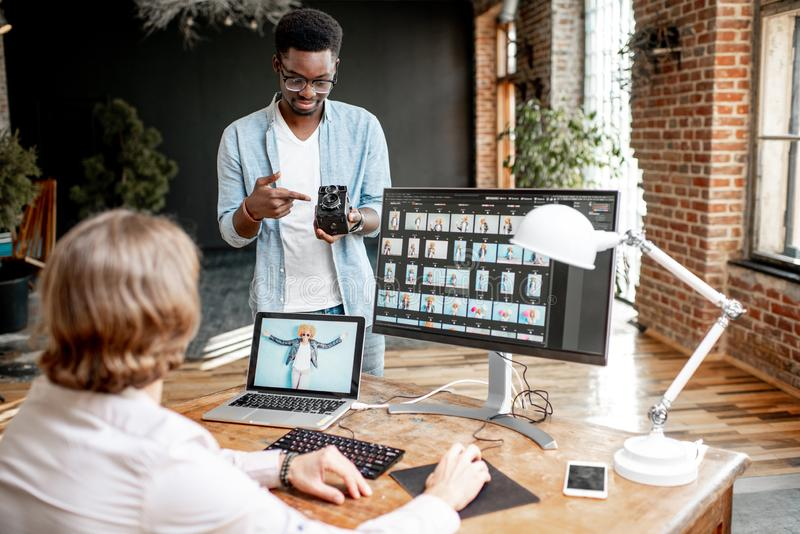 研究计算机的两位摄影师在演播室 免版税库存图片