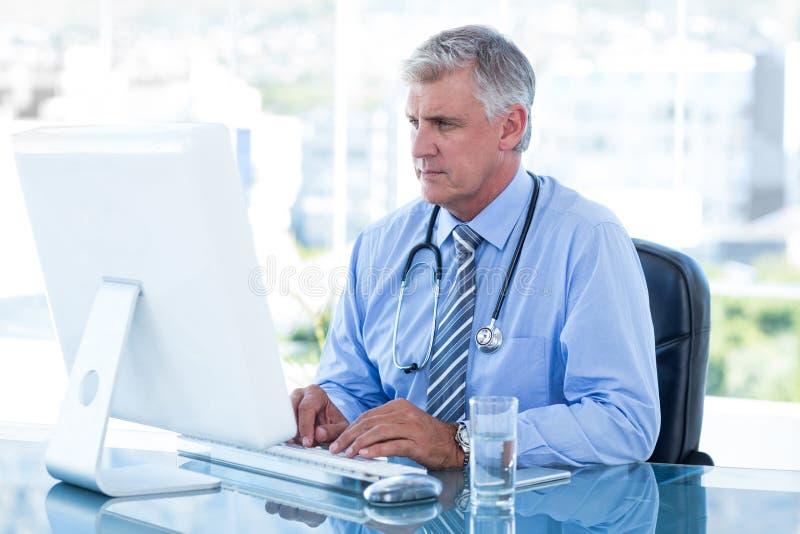 研究计算机的严肃的医生在他的书桌 免版税库存图片