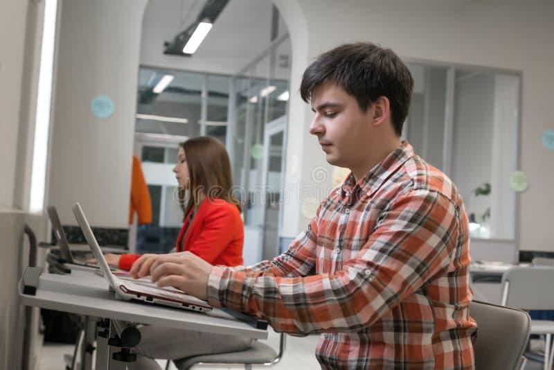 研究计算机的人们在露天场所办公室 免版税库存图片