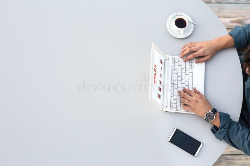 研究计算机的商人在办公室灰色圆桌顶视图 库存照片