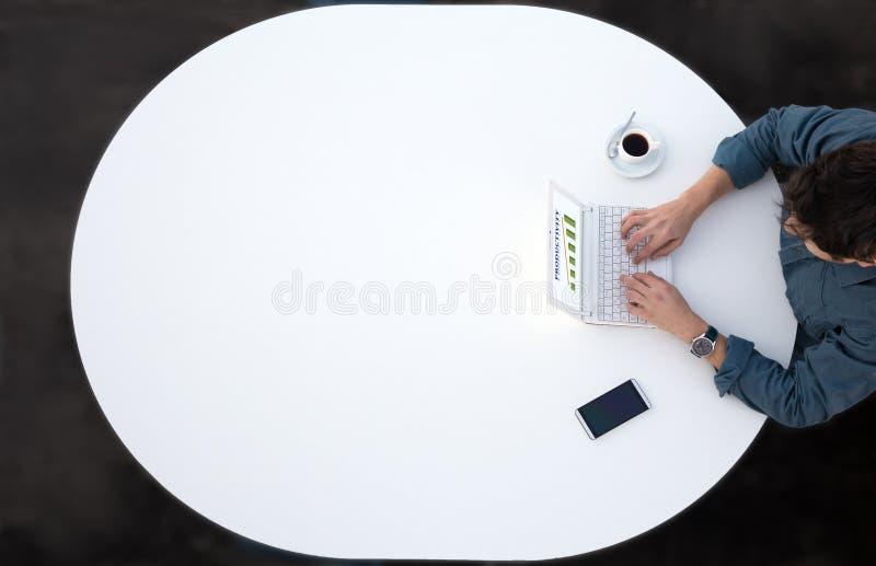 研究计算机的商人在办公室白色圆桌上 库存图片