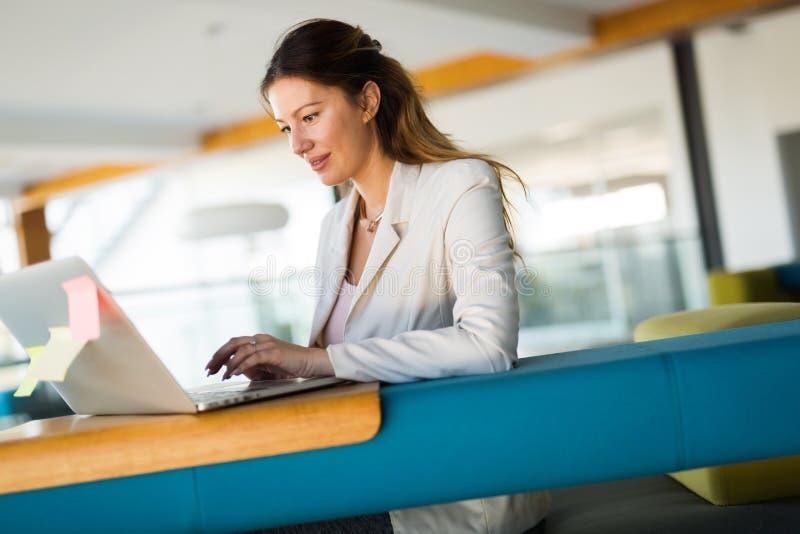 研究计算机的女实业家画象在办公室 库存图片
