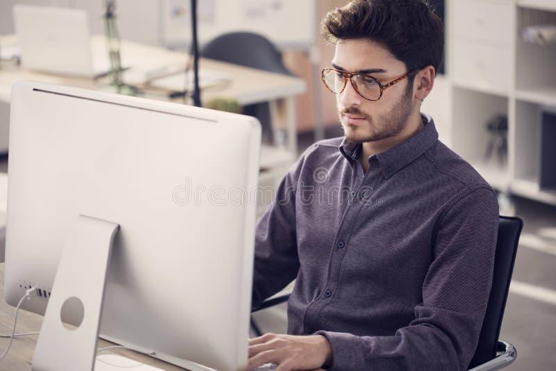 研究计算机的年轻人 免版税库存图片