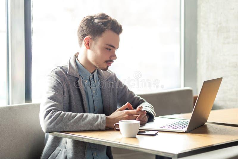 研究计算机的年轻成功的严肃的商人画象坐在办公室 免版税库存照片