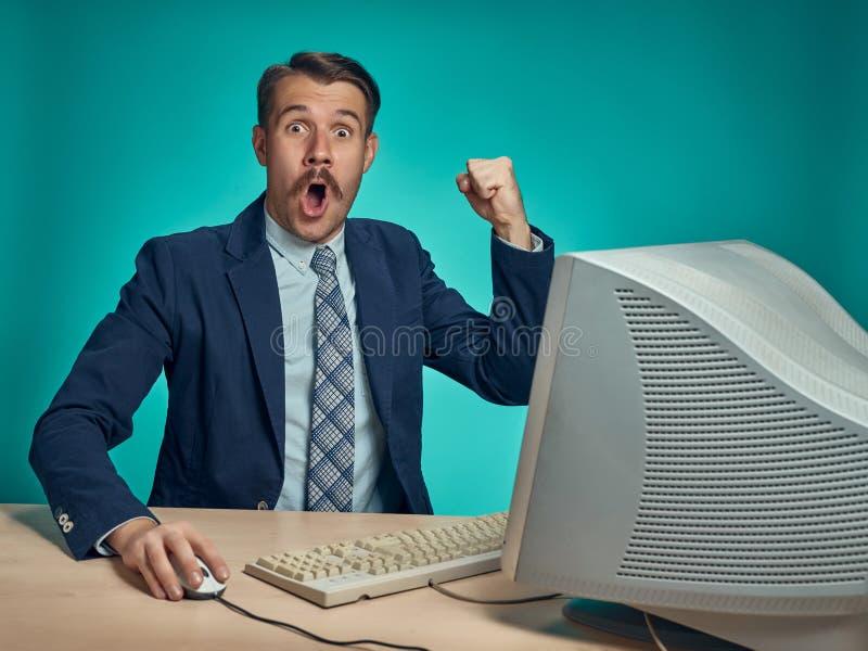 研究计算机的惊奇的年轻人在书桌 免版税库存照片