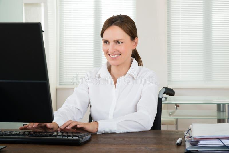 研究计算机的有残障的女实业家 库存照片