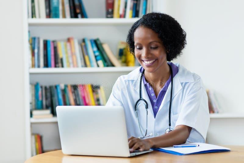 研究计算机的笑的非裔美国人的女性医生 免版税库存图片
