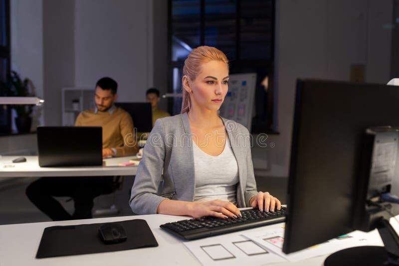 研究计算机的设计师在夜办公室 免版税库存图片