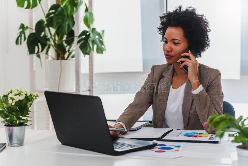 研究计算机的非裔美国人的女实业家在她的办公室 免版税库存图片