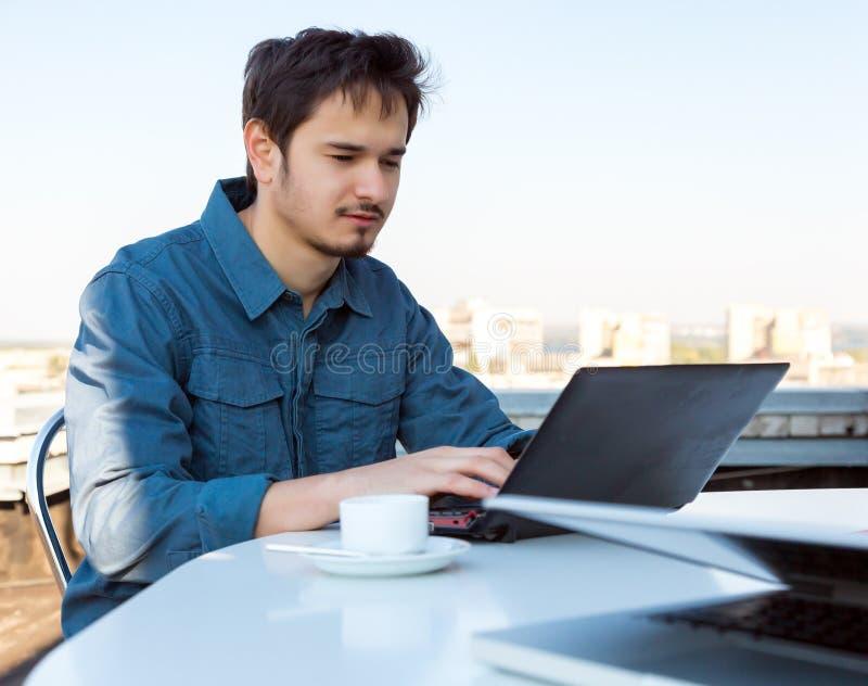 研究计算机的年轻亚洲有胡子的商人 库存图片