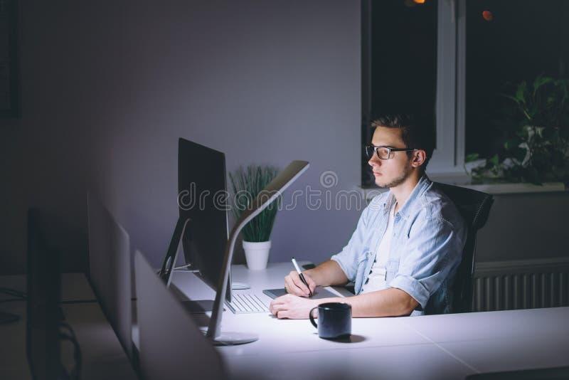 研究计算机的年轻人在晚上在黑暗的办公室 免版税库存照片