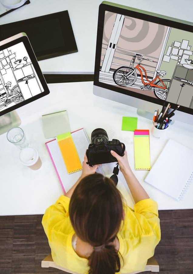 研究计算机的年轻摄影师在新的设计和有照相机的 库存图片