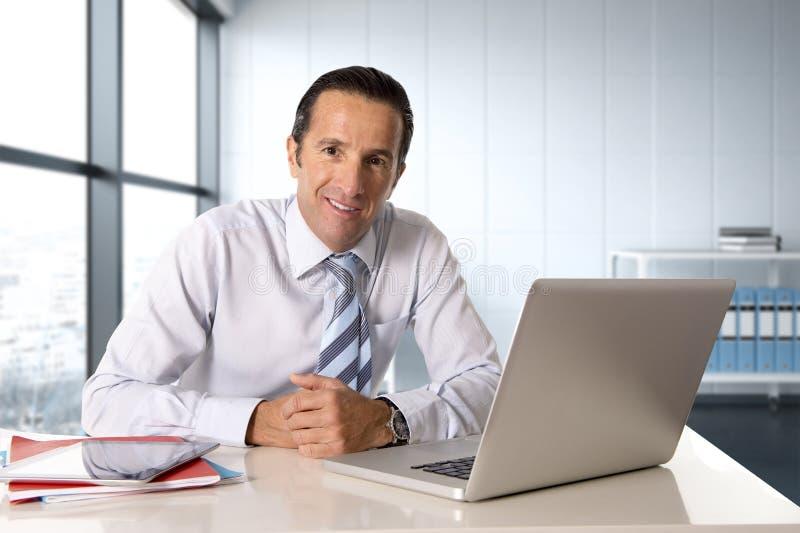 研究计算机膝上型计算机的商人坐在看起来的书桌确信 图库摄影
