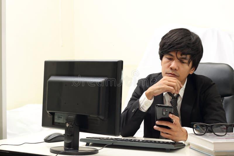 研究计算机,白色背景的商人 免版税库存照片