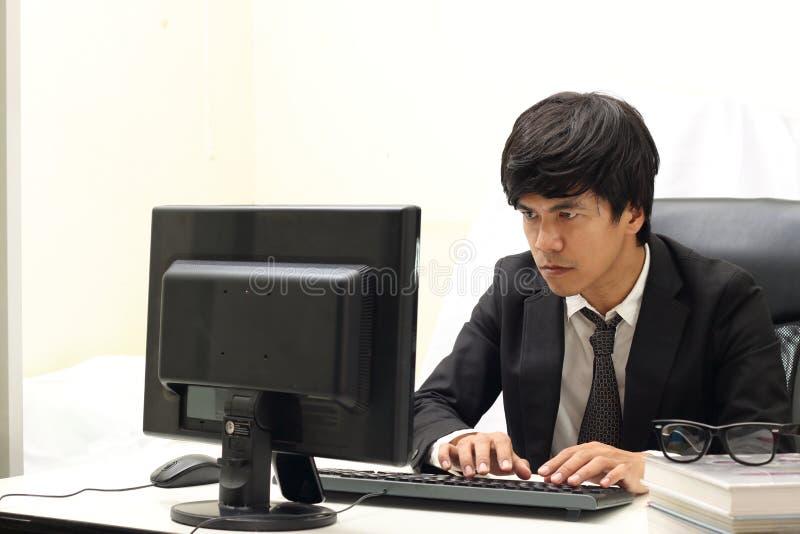 研究计算机,白色背景的商人 免版税库存图片