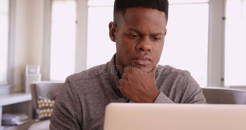 研究从他的家庭办公室的一台膝上型计算机的年轻黑人 免版税库存图片