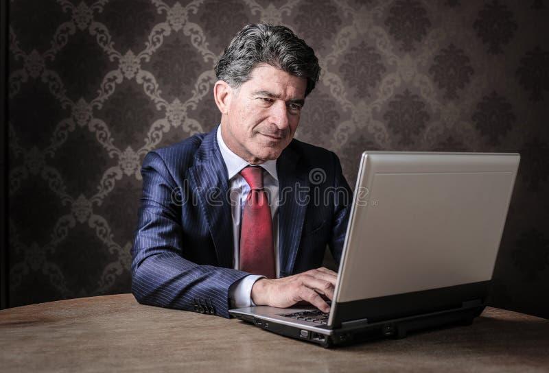 研究他的膝上型计算机的商人 免版税库存照片