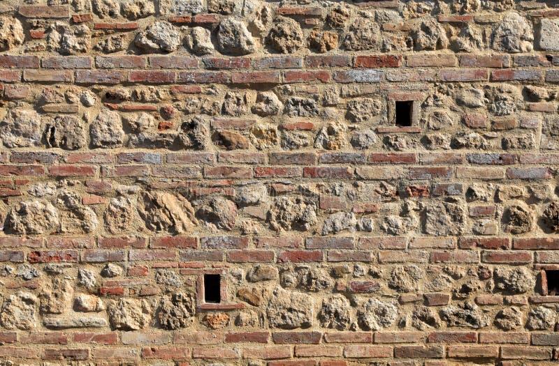 砖和石头中世纪墙壁织地不很细背景 库存图片