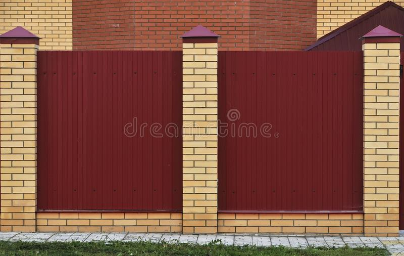 砖和装饰金属围栏 带有黄色元素的红色围栏 高高美丽的击剑 库存照片