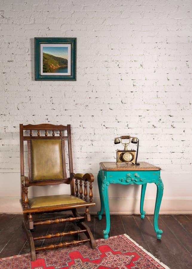 砖墙上的皮革摇椅、木绿色复古桌和古董金电话 免版税库存图片