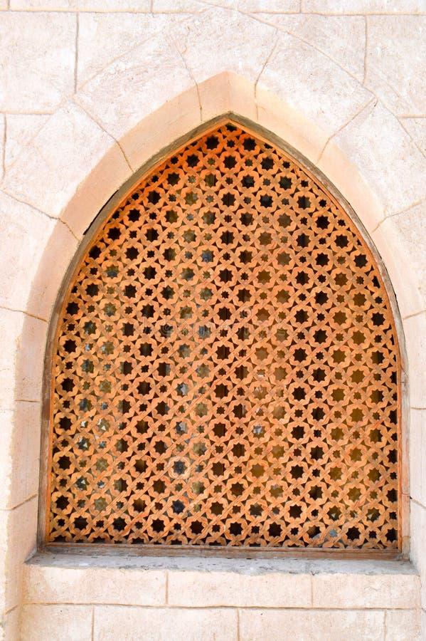砖墙和古老被雕刻的阿拉伯伊斯兰教的伊斯兰教的三角窗口的木棕色老人的纹理与装饰品的 免版税图库摄影