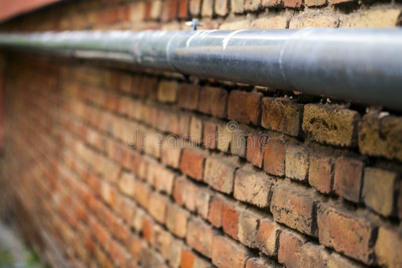 砖墙和水管 免版税库存照片