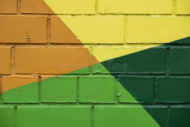 砖墙用明亮的抽象图画油漆特写镜头装饰 详述象作为街道画 背景的片段 免版税库存照片
