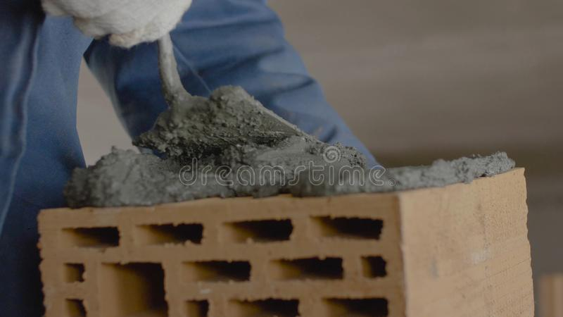 砖墙的建筑 在砖的修平刀传播的水泥 工作者涂砖的水泥 免版税图库摄影