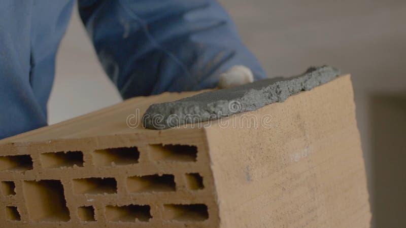 砖墙的建筑 在砖的修平刀传播的水泥 工作者涂砖的水泥 图库摄影