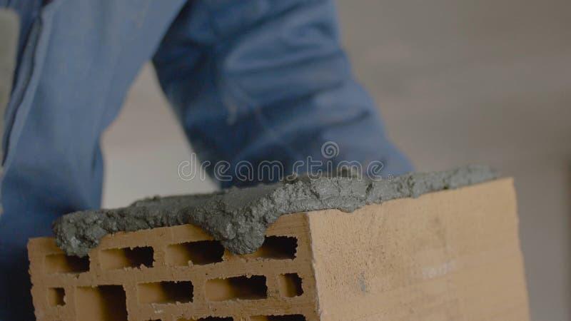 砖墙的建筑 在砖的修平刀传播的水泥 工作者涂砖的水泥 免版税库存照片