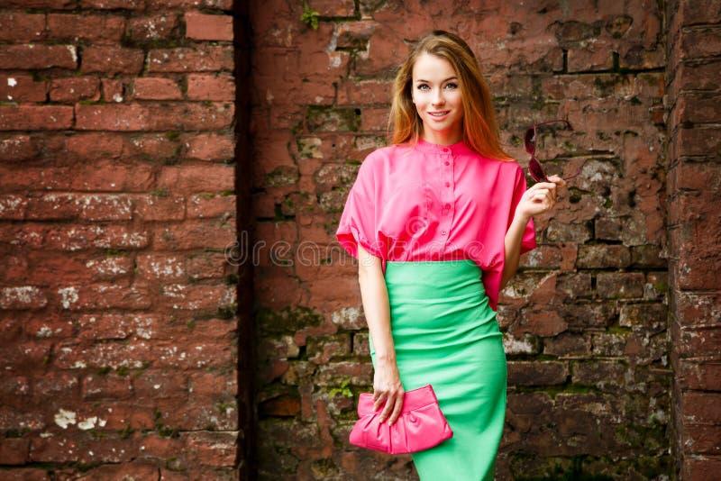 砖墙的愉快的时尚妇女 免版税图库摄影