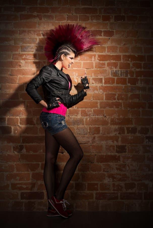 砖墙背景的低劣的女孩 免版税库存图片