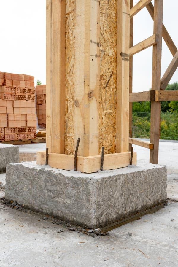 砖房子建筑概念 关闭大厦与木专栏和具体模板的支持元素垂直的照片  免版税库存图片