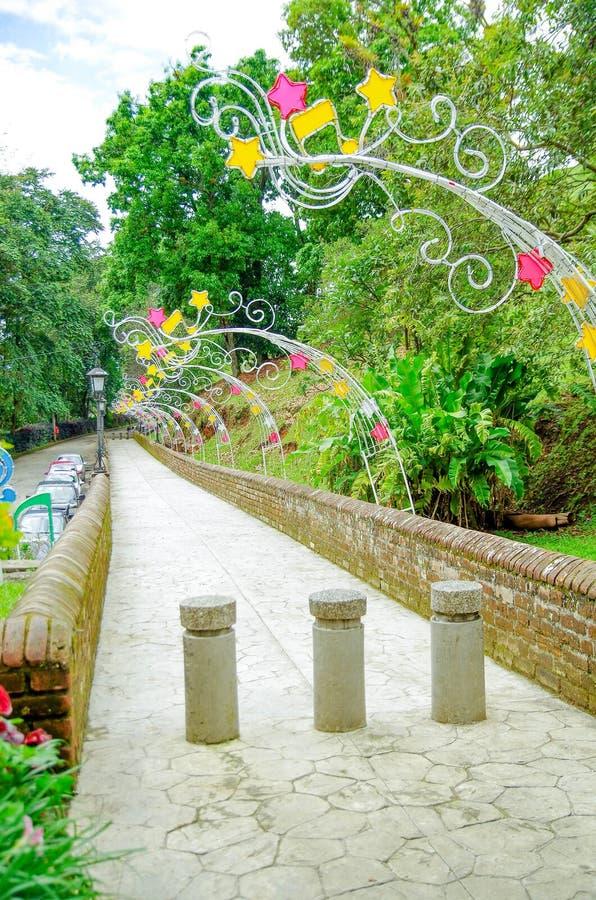 砖桥梁室外看法在有五颜六色的装饰品的殖民地城市波帕扬沿位于哥伦比亚的扔石头的道路 免版税图库摄影