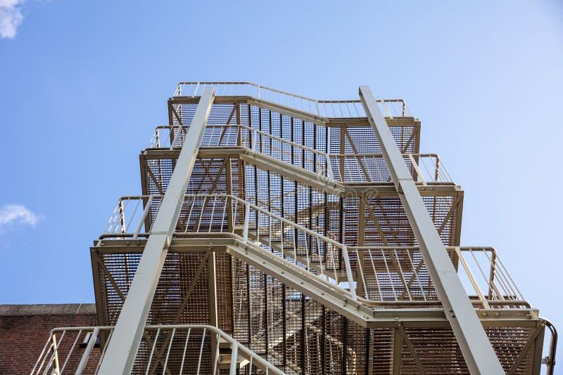 砖瓦房下来逃脱火主导的金属现代台阶 反对蓝天的修造的外在钢楼梯 免版税库存照片
