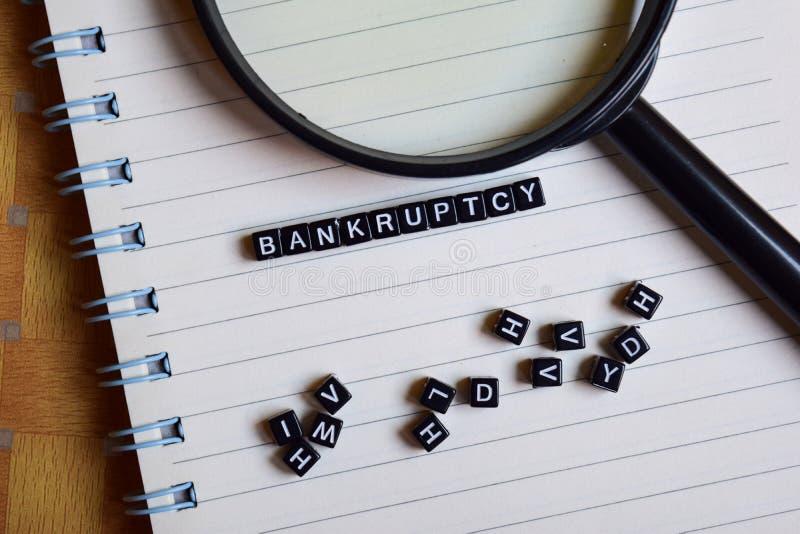 破产的概念在木立方体的与书在背景中 免版税库存图片