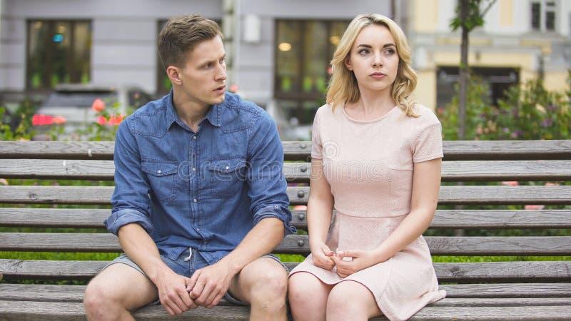 破坏在长凳的男人和妇女在公园,在关系,问题上的冲突 免版税库存图片