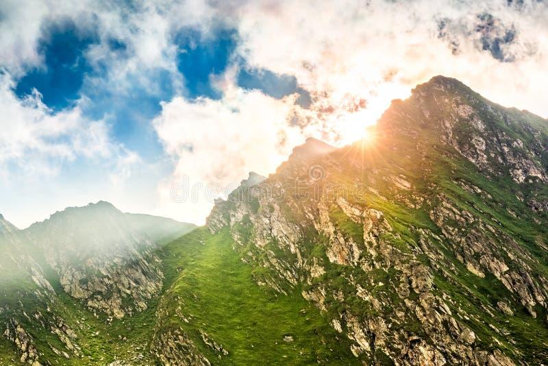 破裂在山峰后的太阳火光 免版税库存图片