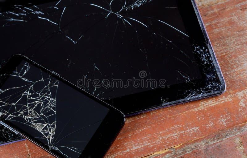 破裂的残破的电话和片剂屏幕特写镜头 免版税库存图片