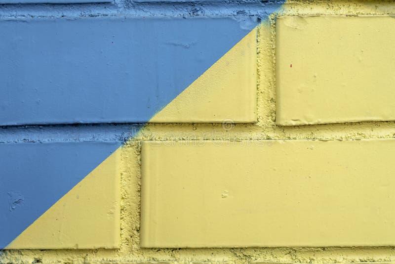 破裂的老砖墙,老切削的油漆,抓痕细节  抽象难看的东西纹理背景,在蓝色和黄色 免版税图库摄影