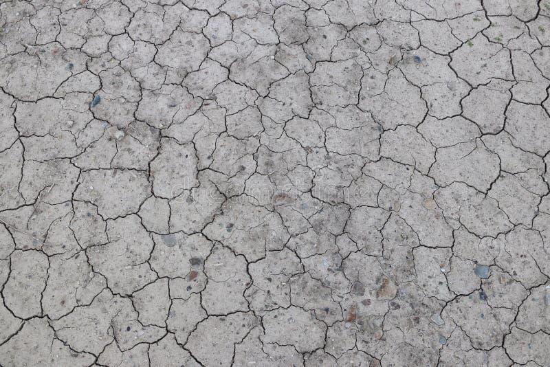破裂,干地球是灰色的 没有水的一片沙漠 干旱的陆运 湿气的干渴在无生命的空间 生态situati 库存照片