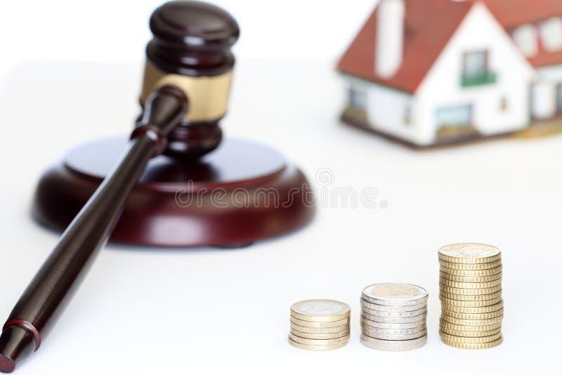 硬币、房子模型和惊堂木 免版税库存照片