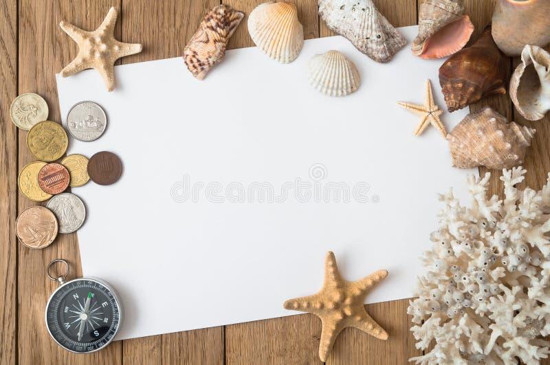 硬币、海壳、星和珊瑚在一张木桌上 旅行co 库存图片