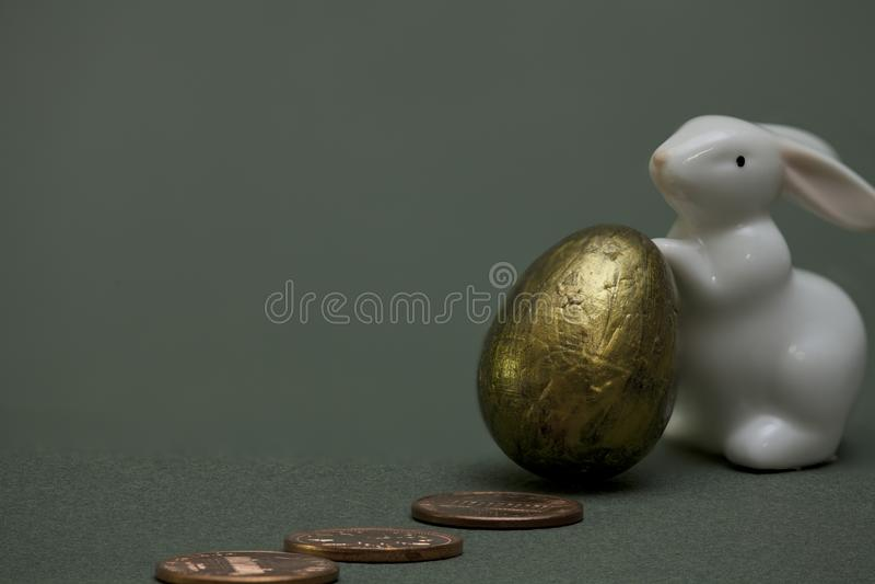 硬币和一只兔子用一个金黄鸡蛋 库存照片