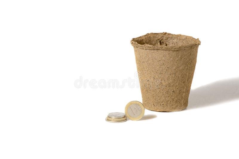 硬币和泥煤罐一起在,在一家农村农业生产公司中的幼木的被隔绝在白色 库存图片